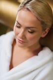 Закройте вверх женщины сидя в робе ванны на курорте Стоковые Изображения