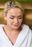 Закройте вверх женщины сидя в робе ванны на курорте Стоковое Изображение