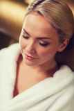 Закройте вверх женщины сидя в робе ванны на курорте Стоковое Фото