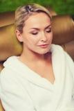 Закройте вверх женщины сидя в робе ванны на курорте Стоковая Фотография