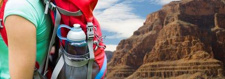Закройте вверх женщины с бутылкой с водой в рюкзаке Стоковые Фото