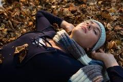 Закройте вверх женщины с руками за головой лежа на сухих листьях Стоковые Фото
