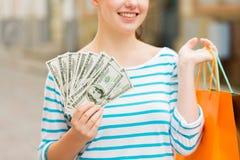 Закройте вверх женщины с хозяйственными сумками и деньгами Стоковое Изображение RF