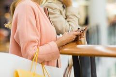 Закройте вверх женщины с smartphone и хозяйственной сумкой Стоковые Фото