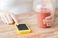 Закройте вверх женщины с smartphone и smoothie Стоковое фото RF