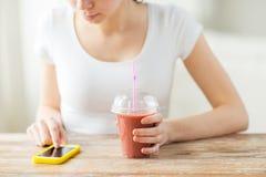 Закройте вверх женщины с smartphone и smoothie Стоковые Фотографии RF