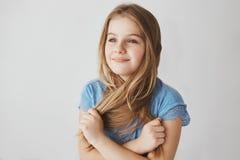 Закройте вверх жизнерадостной малой белокур-с волосами девушки при голубые глазы держа волосы с руками, смотрящ в сторону с счаст Стоковая Фотография RF