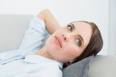 Закройте вверх заботливой женщины ослабляя на софе Стоковое Изображение
