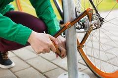 Закройте вверх замка велосипеда крепления человека на автостоянке Стоковая Фотография