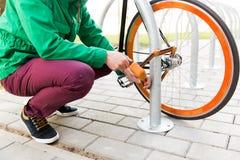 Закройте вверх замка велосипеда крепления человека на автостоянке Стоковое Фото