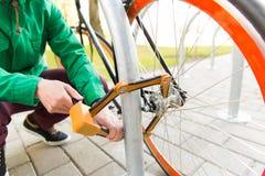 Закройте вверх замка велосипеда крепления человека на автостоянке Стоковое фото RF