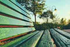 Закройте вверх зеленой деревянной скамьи в городском парке во время времени захода солнца Стоковое Изображение RF