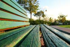 Закройте вверх зеленой деревянной скамьи в городском парке во время времени захода солнца Стоковое Фото
