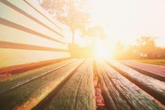 Закройте вверх зеленой деревянной скамьи в городском парке во время времени захода солнца Стоковые Изображения RF