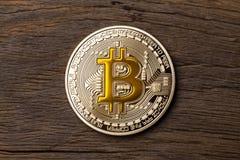 Закройте вверх золотого bitcoin желтого цвета cryptocurrency на деревянном backg Стоковые Изображения RF