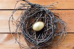 Закройте вверх золотого пасхального яйца в гнезде на древесине Стоковые Фотографии RF
