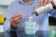 Закройте вверх зрелого человека добавляя сахар к горячему напитку дома стоковые изображения rf