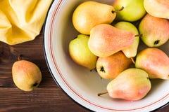 Закройте вверх зрелых груш в плите эмали на деревянном столе Стоковое Изображение