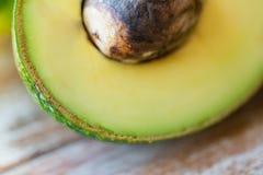 Закройте вверх зрелого авокадоа с косточкой на таблице Стоковое Изображение