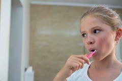 Закройте вверх зубов девушки чистя щеткой Стоковые Фото
