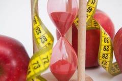 Закройте вверх измерять Metter Процесс тучной потери горения и веса Концепция диеты и фитнеса Красные изолированные яблоки и руле Стоковые Фото