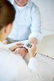 Закройте вверх ИМПа ульс доктора измеряя к старшему человеку стоковое фото rf