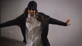 Закройте вверх длинн-с волосами молодой женщины в белой рубашке, черных брюках, куртке и черной крышке скача и показывая современ акции видеоматериалы