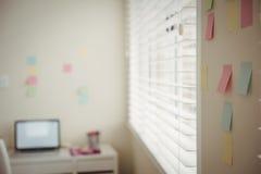 Закройте вверх липких примечаний на стене компьтер-книжкой на таблице Стоковое Изображение