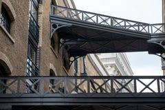 Закройте вверх исторического, восстановленного здания склада причала ` s Батлера и проутюживьте мосты на Shad Темзе, Лондоне стоковые изображения