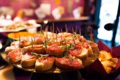 Закройте вверх итальянской еды aperitivo стиля, небольшого bruschette с салями для того чтобы отпраздновать счастливый час внутри стоковое фото rf