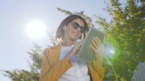 Закройте вверх кавказской занятой коммерсантки которая использует планшет пока она стоит около центра офиса во время a акции видеоматериалы
