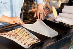 Закройте вверх кашевара жаря блинчики на уличном рынке Стоковые Фотографии RF