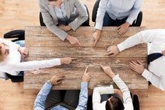 Закройте вверх команды дела сидя на таблице Стоковое Изображение