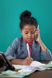 Закройте вверх коммерсантки используя телефон пока пишущ на книге бумажными деньгами Стоковые Изображения