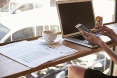 Закройте вверх коммерсантки работая в кофейне используя телефон Стоковые Фото
