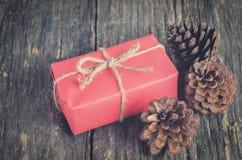 Закройте вверх конуса сосны и красного подарка коробки Стоковые Фотографии RF