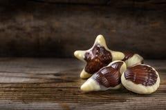 Закройте вверх конфеты seashells над древесиной Стоковое Изображение