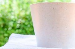 Закройте вверх кофейной чашки на полотенцах ванны с светлым bokeh Стоковая Фотография RF