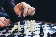 Закройте вверх коллег бизнесмена рук уверенно играя шахмат Стоковое Изображение