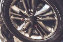 Закройте вверх колеса балансируя на специальном механическом инструменте оборудования в ремонте автомобилей Стоковое Фото