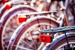 Закройте вверх колеса велосипедов на автостоянке в городе Солнечный свет Sunsh Стоковое Фото