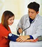 Закройте вверх красивого молодого доктора с стетоскопом вокруг его шеи принимая ИМП ульс к молодой женщине с a Стоковая Фотография