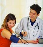 Закройте вверх красивого усмехаясь молодого доктора с стетоскопом вокруг его шеи принимая ИМП ульс к молодой женщине с a Стоковое Изображение RF