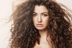 Закройте вверх красивой девушки при вьющиеся волосы смотря камеру над розовой предпосылкой Стоковые Фото