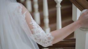 Закройте вверх красивой невесты идя вниз с лестниц Женщина в белом платье приходит вниз с лестниц движение медленное видеоматериал