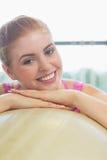 Закройте вверх красивой склонности женщины на шарике тренировки Стоковое Изображение