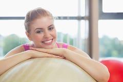 Закройте вверх красивой склонности женщины на шарике тренировки Стоковое Фото