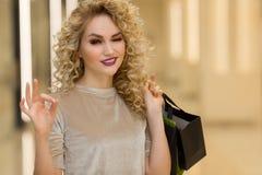 Закройте вверх красивой счастливой женщины с хозяйственными сумками усмехаясь и показывая о'кеы в моле Стоковое Фото
