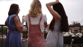 Закройте вверх красивых беспечальных женщин вися вне на балконе Выпивая коктеили, танцуя daytime Взгляд задней стороны сток-видео