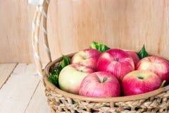 Закройте вверх красивых яблок в плетеной корзине на деревянном backgrou Стоковое фото RF